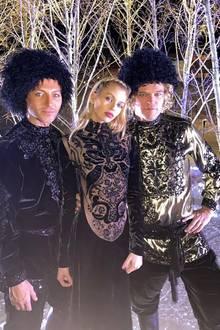 Model Stella Maxwell zeigt sich in einem schwarzen, schweren Samtgewand mit goldenem Brokatund posiert zwischen Evangelo Bousis sowie Modedesigner Peter Dundas. Ihre Looks passen bestens in das winterliche St. Moritz, wo die Hochzeit stattfindet.