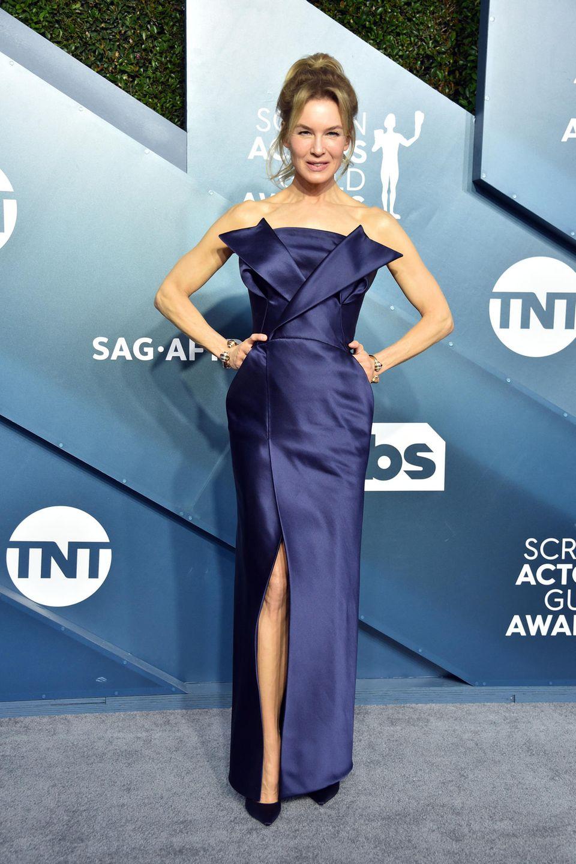 Renée Zellweger zeigt sich selbstbewusst in Maison Margiela und High Heels von Jimmy Choo. Ihr Schmuck ist von Cartier.