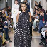 Was für eine Robe: Das französische Modelabel Lanvin zeigt auf dem Runway ein bodenlanges Kleid mit Raffungen am Hals und Volants am Saum. Bella Hadid präsentiert das Kleid außerdem mit langen schwarzen Handschuhen.