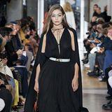 Auch ihre Schwester Gigi Hadid läuft für das Kultlabel Lanvin. Das schwarze, bodenlange Kleid besticht durch ein Cape am Rücken und ein tiefes V-Dekolleté. Volants am Saum perfektionierenauch diese Traum-Robe.