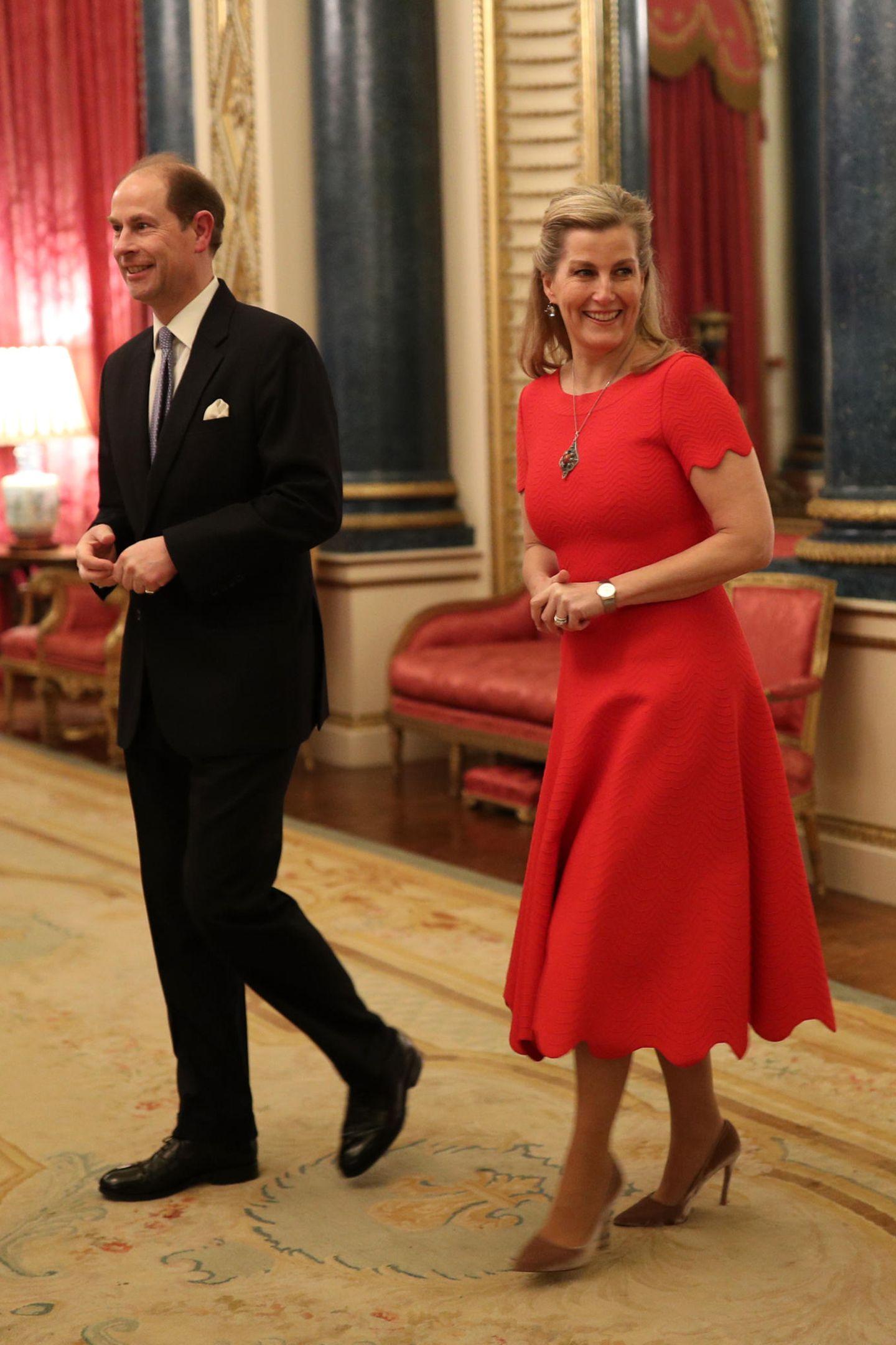 """Sophie, Gräfin von Wessex, die an diesem Tag Geburtstag feiert, entscheidetsich für ein knallrotes Jacquard-Midi-Kleid von """"Azzedine Alaïa"""". Niedliche Wellen-Details an den Ärmeln, halb-hochgestecktes Haarund eine große Kette machen den verspielten Look perfekt."""