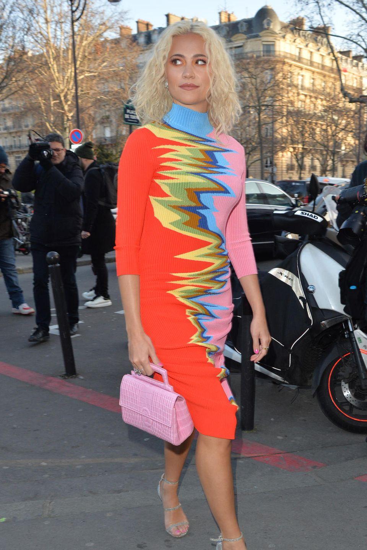 Ein stylischer Hingucker abseits des Runways ist Sängerin Pixie Lott. In einem knalligen Rollkragenkleid mit glitzerfarbenen Stilettos und einer rosefarbenen Tasche macht sie sich zu einem häufig fotografierten Motiv der Pariser Fashion Week.