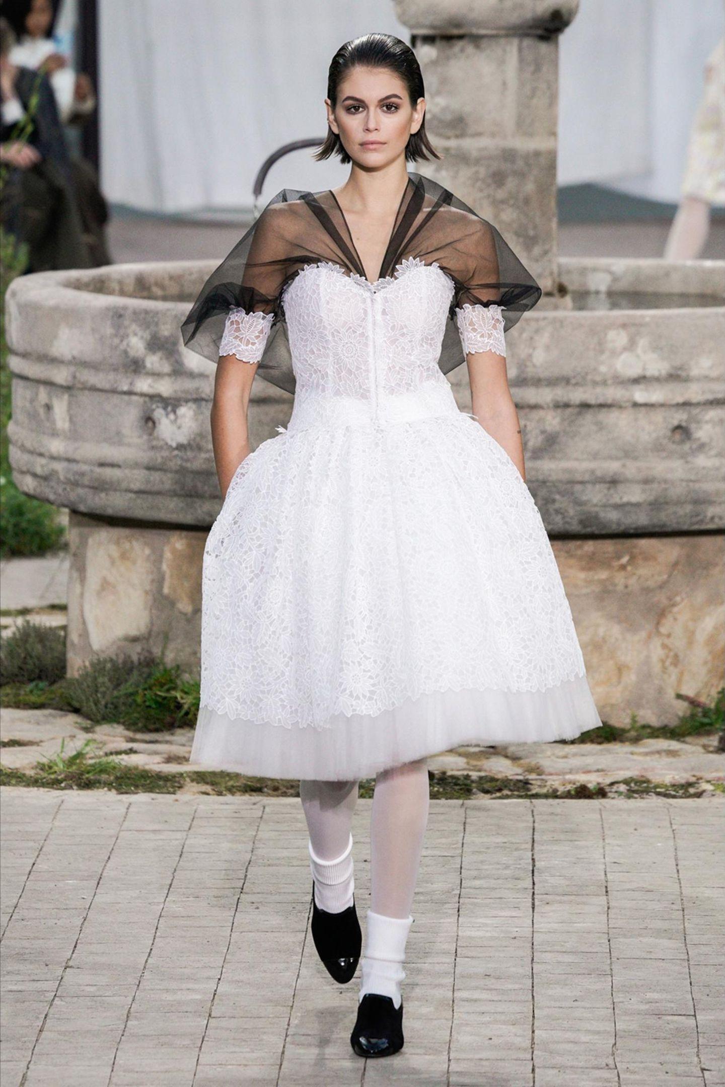 Kaia Gerber präsentiert eine Chanel-Kreation aus Spitze und Organza. Der Tellerrock zaubert eine großartige Silhouette.