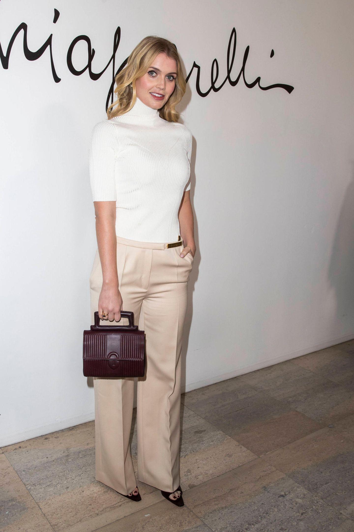 Lady Kitty Spencer erscheint zur Fashionshow von Schiaparelli in einem weißen Rollkragenpullover in Kombination mit einer weit geschnittenen Stoffhose.