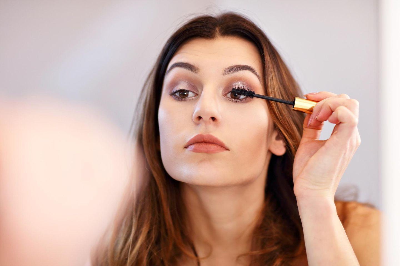 Frau tuscht sich vor dem Spiegel die Wimpern