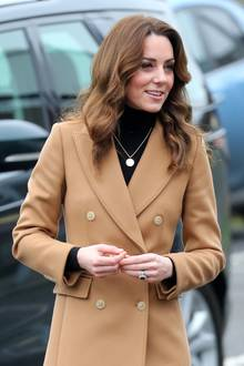 Eine goldene Kette mit einem kreisförmigen Anhänger ergänzt Kates schlichtes Outfit perfekt und sorgt für einen Hingucker.