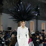 Der Designer setzt sogar noch einen drauf und kreiert zum weißen Anzug mit Bermuda-Shorts einen XXL-Federfächer für die Haare.