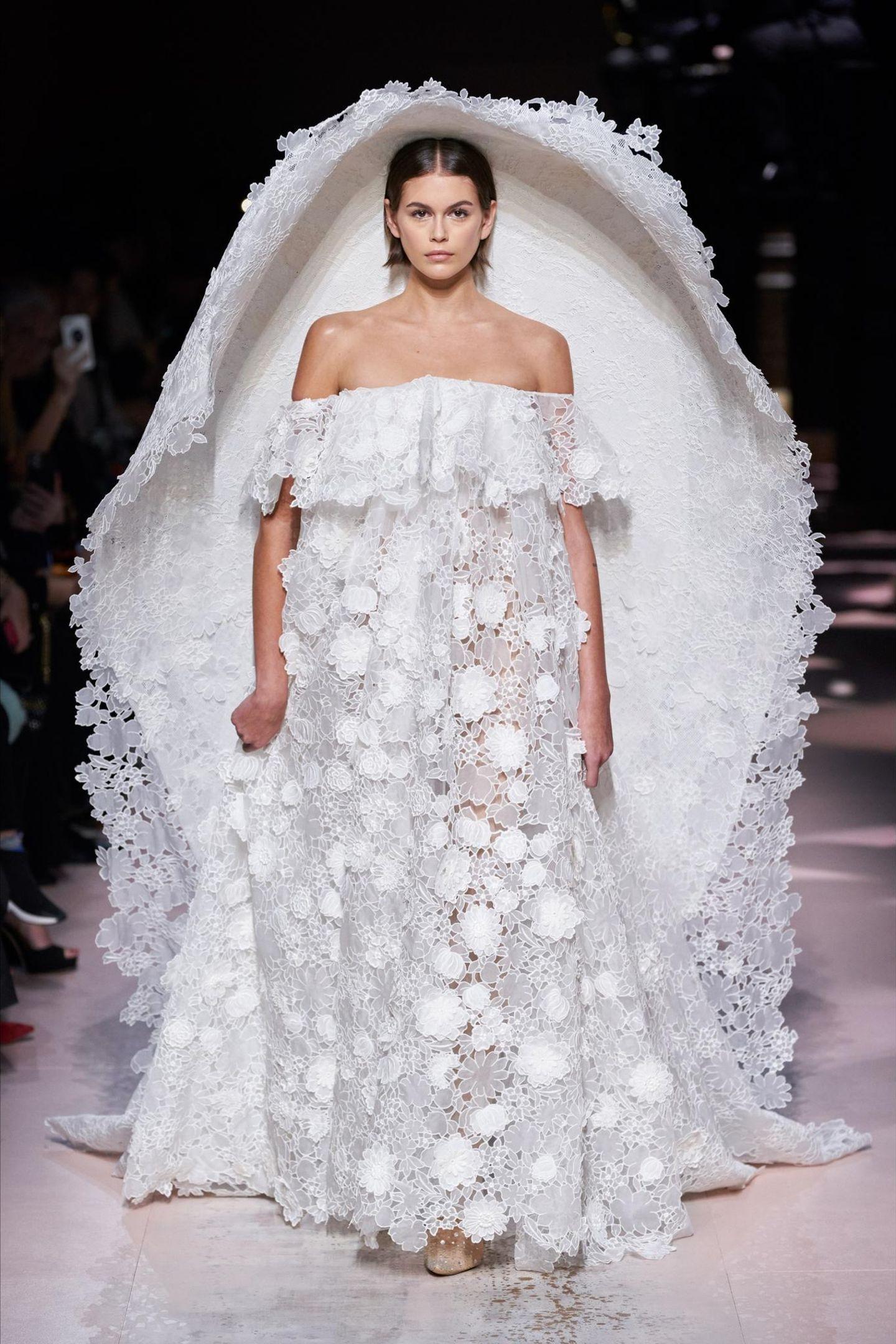 Ein ganz besonderes Highlight darf Kaia Gerber während der Haute Couture Fashion Show des Luxus-Labels Givenchy präsentieren. Zugegeben: Für das Hochzeitskleid mit Off-Shoulder-Ausschnitt,XXL-Cape und dreidimensionaler Blütenspitze muss die Braut in Spe eine Portion Mut aufbringen.
