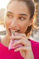 Sportliche Frau isst einen Müsliriegel