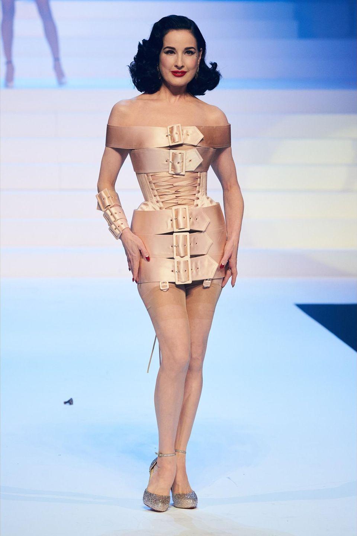 Auch Dita von Teese läuft in einem Mini-Kleid mit Statement-Schnallen und Korsageüber den Laufsteg des französischen Modeschöpfers Jean Paul Gaultier.