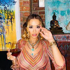 Rita Ora postet sich mit einem Gläschen Wein – da schaut aber kaum jemand hin, denn ihr transparentes Oberteil gibt mehr preis als es verdeckt.