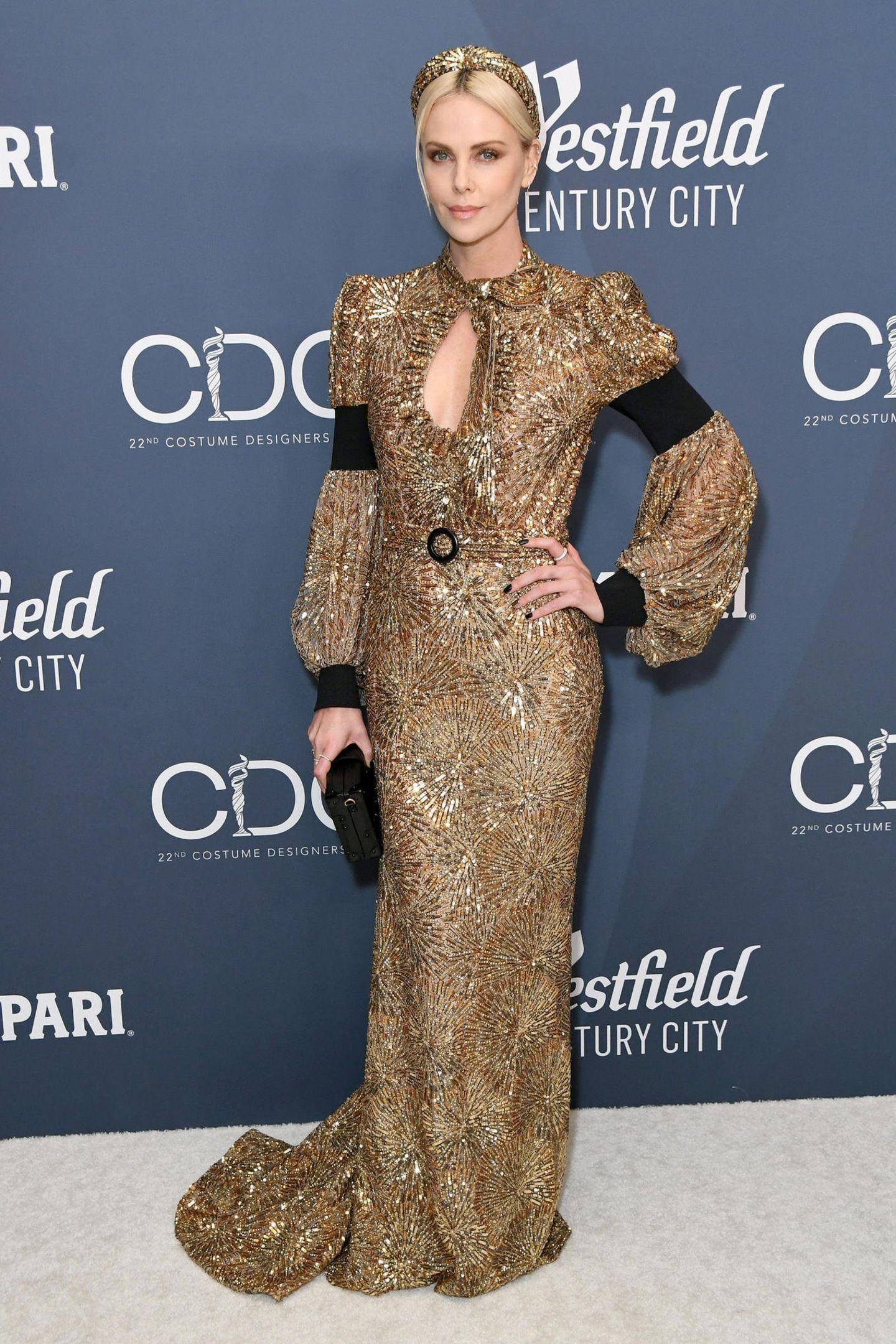 Golden Lady: Schauspielerin Charlize Theron strahlt in einergoldenenLuis-Vuitton-Robe mit Ballonärmeln, Schleppe und Tropf-Dekolleté. Gekrönt wird ihr glamouröser Look durch einen farblich passenden Haarreifen,schwarz lackierte Fingernägel und Metallic-Lidschatten.