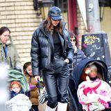 Sie trägt eine schwarz-glänzende Daunenjacke und eine schwarze Lederhose. Dazu kombiniert sie weiße Cowboystiefel von Sam Edelmanund eine Mini-Bag mit Kuhfellmuster, ihr Blick ist gesenkt.