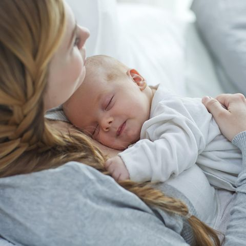 Haarausfall nach Schwangerschaft, Baby liegt bei Mutter auf der Brust und hält ihren Zopf fest