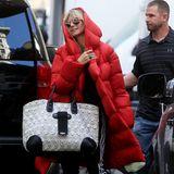 """In eine dicke rote Daunenjacke gepackt, mit UGG-Boots und Sonnenbrille erscheint Heidi Klum am Set von """"Germany's next Topmodel"""" in Los Angeles. Sie trägt eine schwarze Jogginghose und hat eine große Tasche dabei. Sie wirkt leicht gestresst und als wolle sie unerkannt bleiben."""
