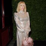 Courtney Love erscheint in einem hochgeschlossenen hellen Kleid. Das Federtäschchen ist perfekt auf ihren rosafarbenen Lippenstift abgestimmt.