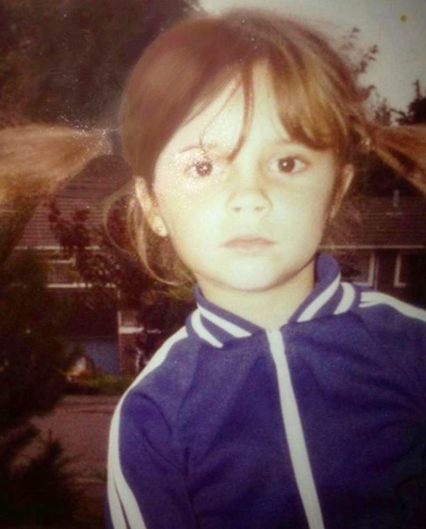 """Victoria Beckham  Mit frechen Zöpfchen und Trainingsjacke schaut die kleine Victoria Beckham entschlossen in die Kamera. Die strenge Miene beherrscht """"Posh Spice""""offensichtlich schon von Kindheitstagen an. Vielleicht ahnt sie bereits, dass ihre Disziplin ihreines Tages zu einer großen Karriere verhilft."""