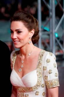 Das weiße Kleid ist mit Hibiskusblüten (der Nationalblume von Malaysia)bestickt. Zu dem Vintage-Dress kombiniert die Herzogin neuen Schmuck von Van Cleef & Arpels.