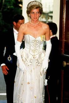 In einem ähnlichen Look kam Prinzessin Diana 1986 zum Bankett in der deutschen Botschaft in London. Das harmonische Zusammenspiel ausweißer Spitze und goldenen Bestickungen überzeugt sowohl im orientalischen Stil, wie bei Kate oder als klassisches Abendkleid bei Diana.