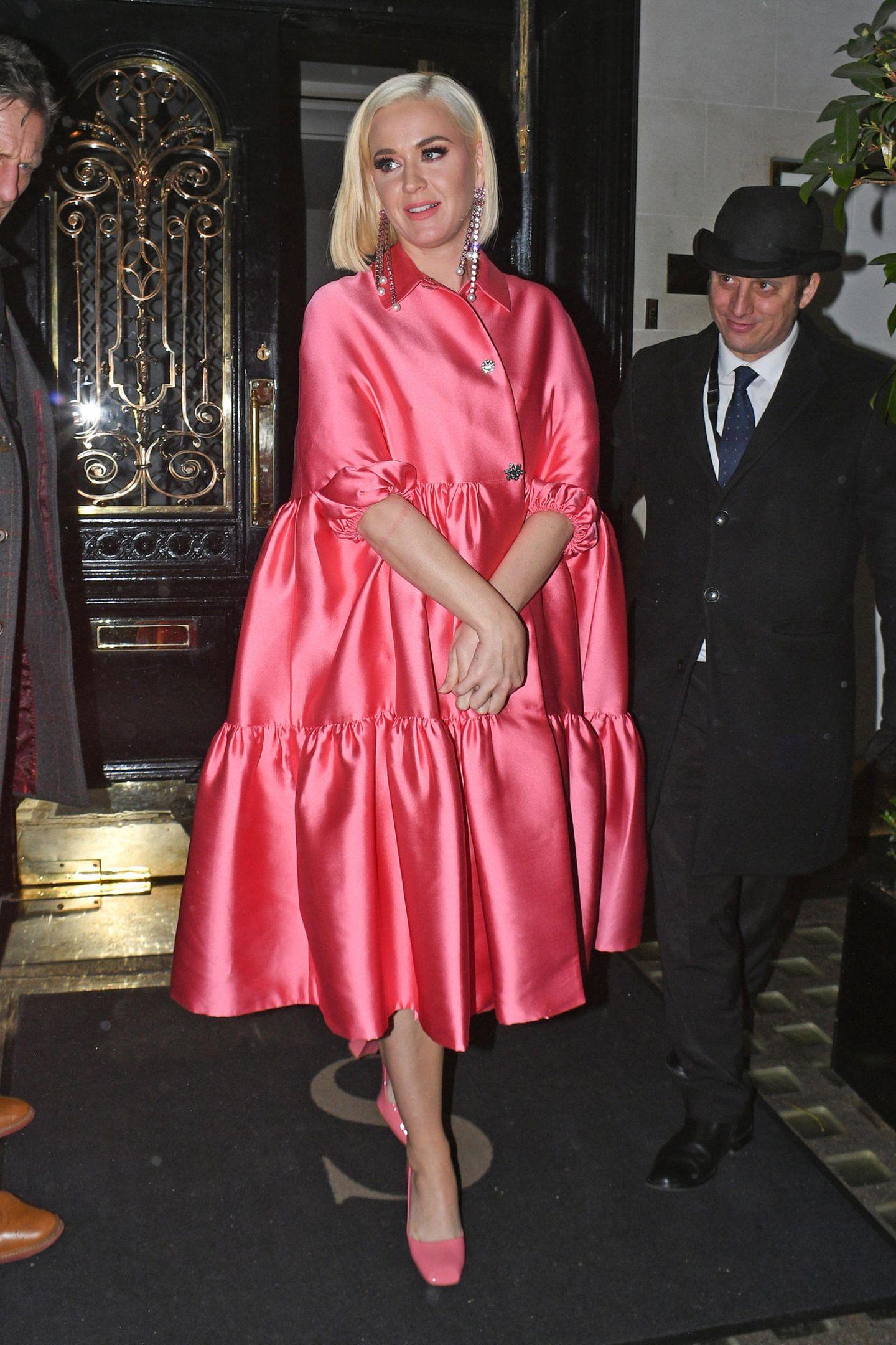 Pinker geht es wohl nicht. Katy Perry macht London in einem hochwertigen Barbie-Outfit unsicher. Der Look, bestehend aus Off-shoulder-Kleid und Mantel von Lela Rose und pinken Lack-Pumps von Prada harmoniert ungemein mit ihremplatinblonden Haar. Perfektioniert wird der Barbie-Style durch die XXL-Strassohrringe von Christopher Kane.