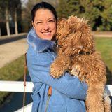 Rebecca Mir trägt ihren Hund auf dem Arm