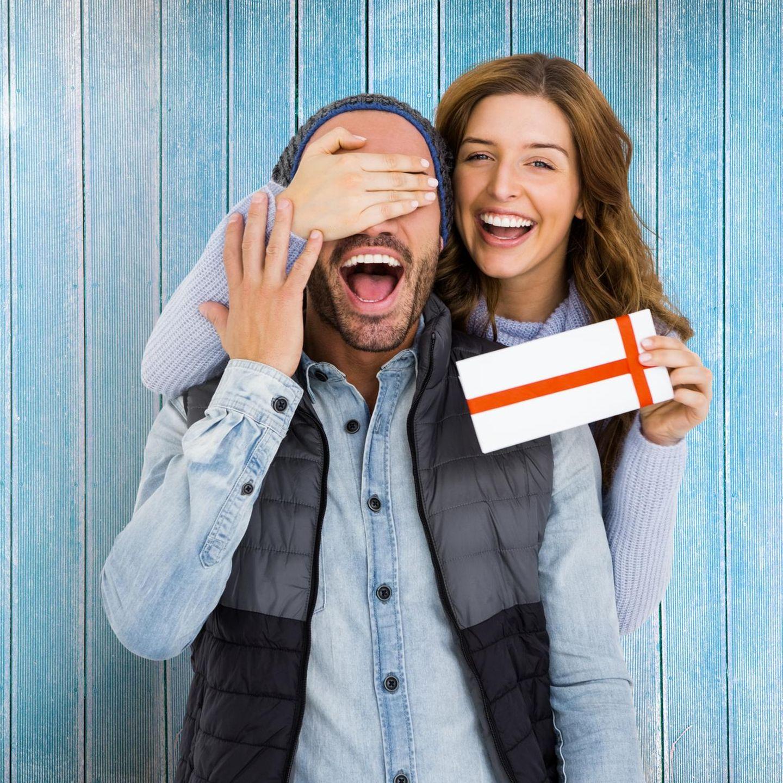 Valentinstagsgeschenke für Männer, Frau überrascht Mann mit Geschenk