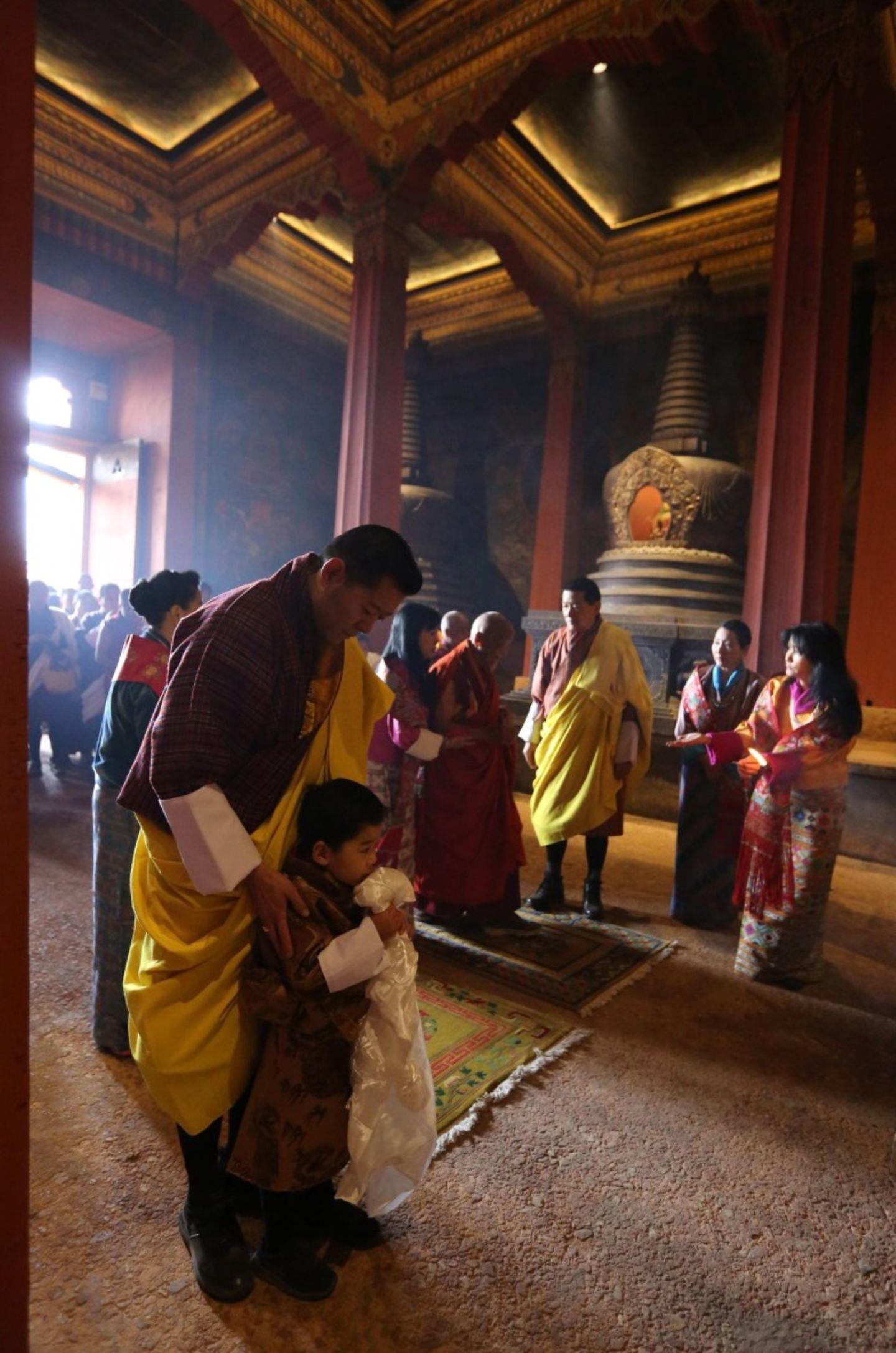 König Jigme legt schützend die Hände auf die Schultern seines Sohnes Prinz Jigme Namgyel Wangchuck. Das Geburtstagskind schaut noch ein wenig skeptisch angesichts der beeindruckenden Zeremonie, der er beiwohnt.