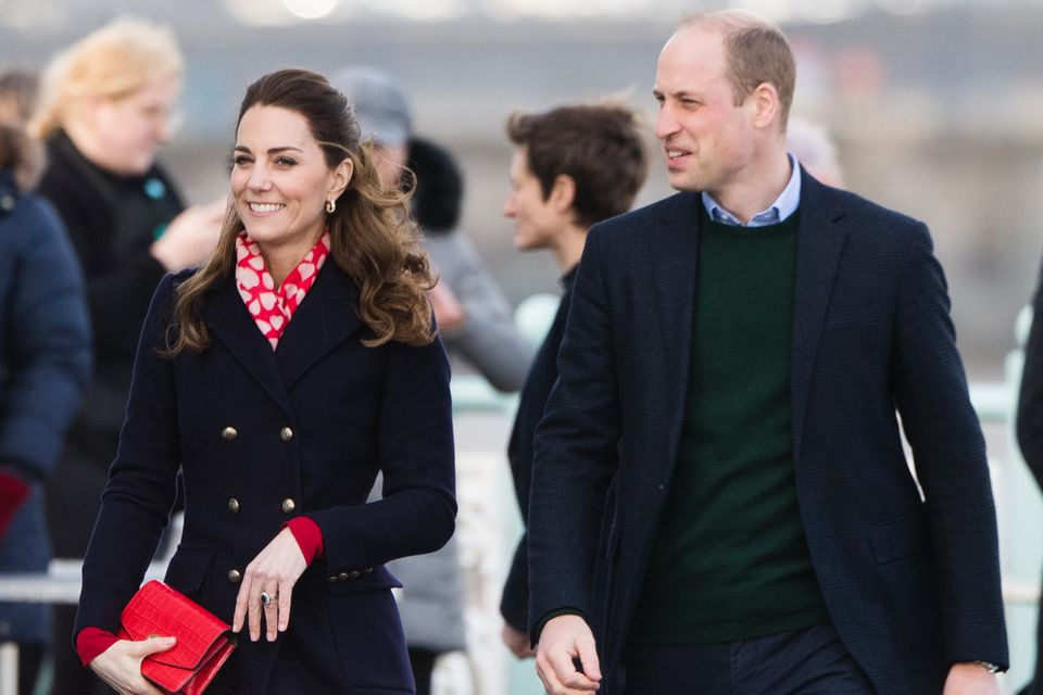 Bei ihrem Besuch in Süd-Wales trägt Herzogin Catherine einen dunklen Mantel über einem roten Kleid. Farblich abgestimmte Accessoires machen den Look perfekt.