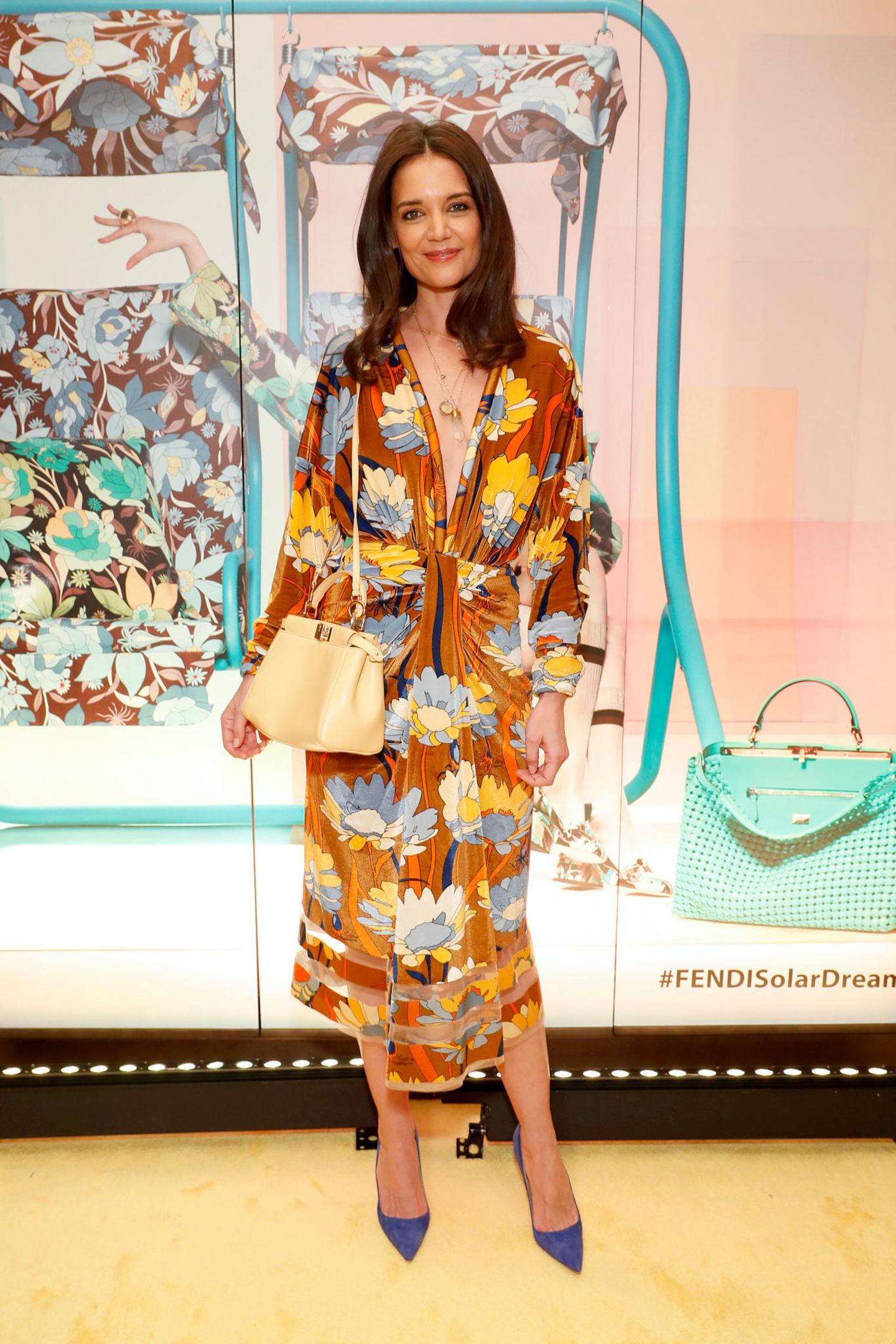 Im perfekten 70s-Look von Fendi trifft man Katie Holmes auf der Fashion Week in New York. Zum gemusterten Kleid mittiefem Ausschnitt kombiniert sie eine beigefarbene Tasche und blaue Wildlederpumps.