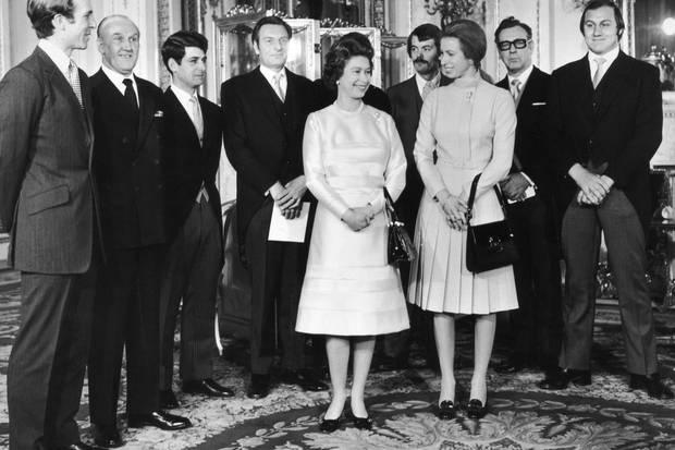 Queen Elizabeth (l.) und Prinzessin Anne (r.) mit ihren Rettern am 26. November 1974 im Palast.