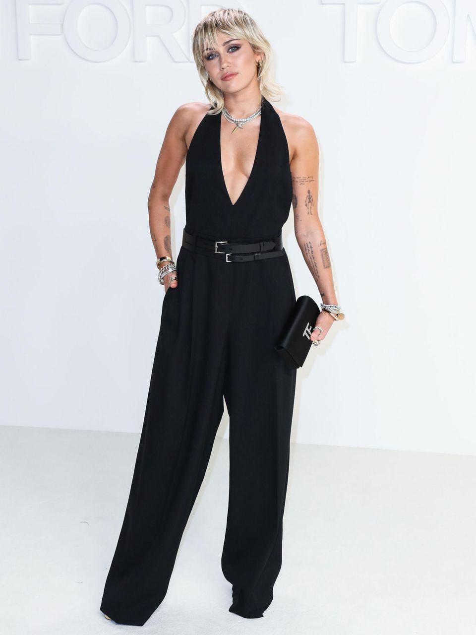 Sängerin Miley Cyrus erscheint zur Fashion-Show in New York in einem tiefdekolletierten Overall mit weiten Bein und Neckholder-Schnitt. Zwei Gürtel in der Taille zaubern der hübschen Blondine eine schlanke Silhouette.
