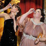 2012: Weg damit!  Rose Byrne und Melissa McCarthy gönnen sich auf der Oscar-Bühne einen kleinen Drink für die Nerven.