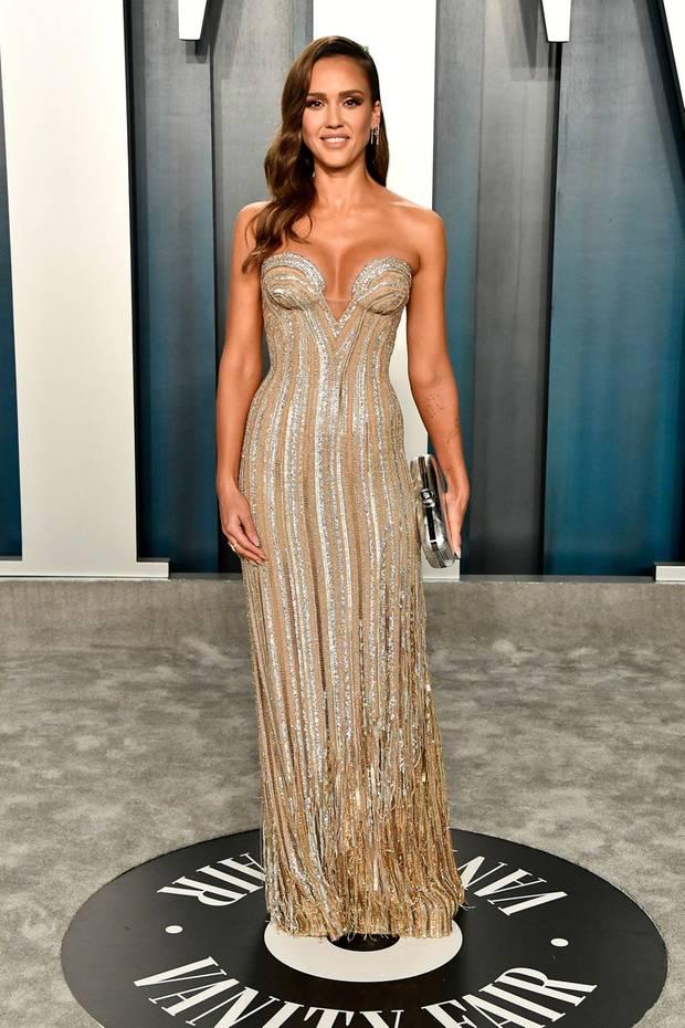 Jessica Alba trägt ein Kleid aus glitzernden Metallicstreifen in Gold und Silber. Die Robe von Versace betont ihre Silhouette perfekt.