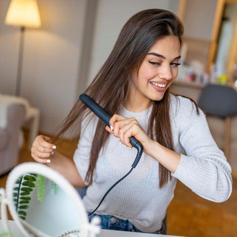 Glätteisen, Frau glättet Haare vor Spiegel