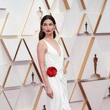 Lily Aldridge setzt mit roter Blüte auf weißem Kleid einen hübschen Akzent.
