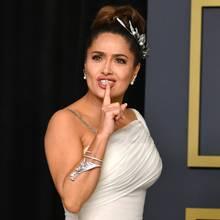 """Psst, schaut mal auf meine Diamanten! Salma Hayekträgt bei den Oscars 2020 die """"Feuilles de Laurier""""-Kette von Boucheronaus Weißgold mit Perlmutt, Südseezuchtperlen und Diamantpavéals Haarband. Dazu kombinierte sie die passenden Ohrringe und den """"Feuilles d´Acanthe""""-Armreif aus Weißgold mit Diamantpavé."""