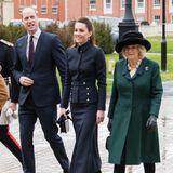 Zu ihrem Ensemble kombiniert Herzogin Kate schwarze Wildlederstiefel von Ralph Lauren, eine schwarze Ledertasche – ebenfalls von Alexander McQueen –sowiefunkelnde Ohrringe von Mappin & Webb.