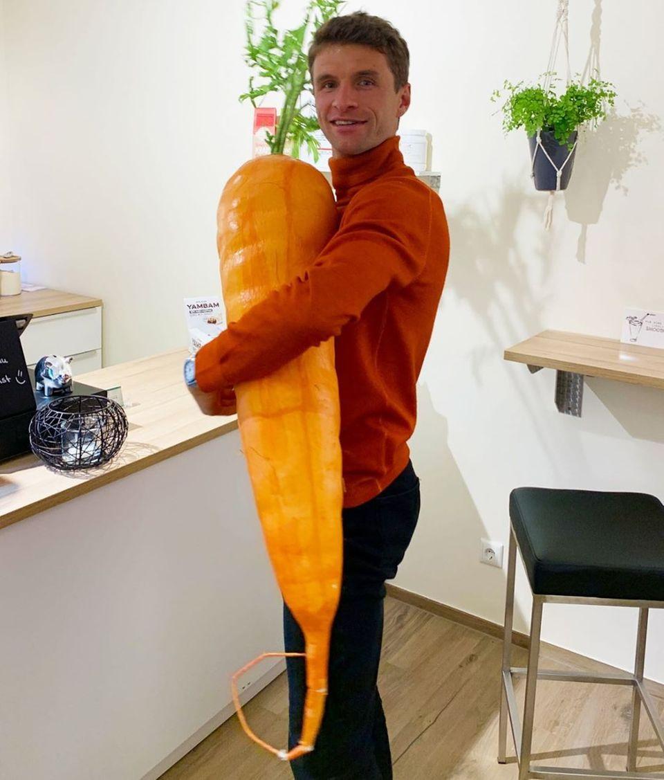 Thomas Müller hält eine riesige Plastik-Karotte