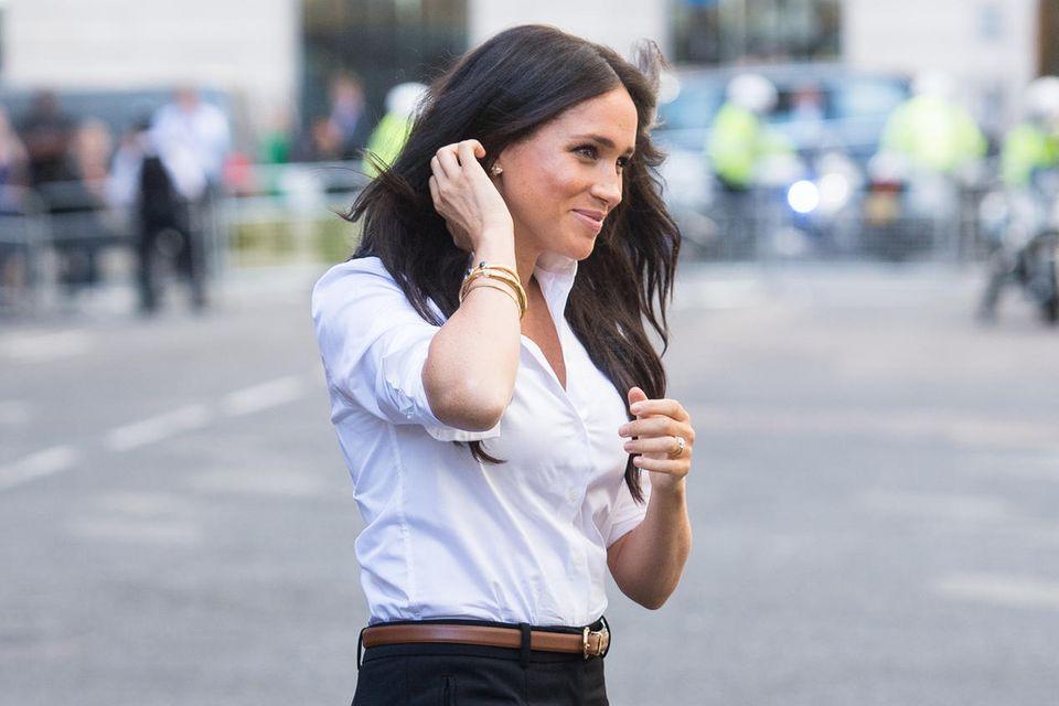 """Herzogin Meghan in ihrer eigenen Modelinie: Für """"Smart Works"""" designte sie unter anderem eine schwarze Hose und eine schicke weiße Bluse."""