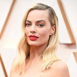Zu Margot Robbies Vintage Robe von Chanel passen tiefer Seitenscheitel und feuerroter Lippenstift perfekt.