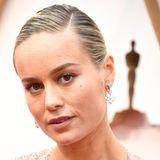 Brie Larson wirktwie ungeschminkt, der Fokus liegt eindeutig auf ihren sleek nach hinten gestylten Haaren.