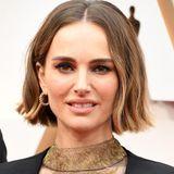 Natalie Portman bringt Glamour auf den Red Carpet: ihre Augen funkeln dramatisch in schwarz-goldenen Tönen. Der Rest des Make-Ups bleibtnatürlich, der Bob ist zu leichten Wellen gestylt.