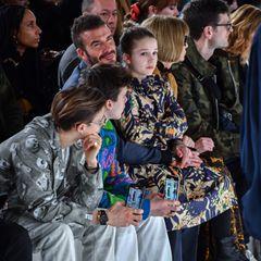 Zu ihrem eleganten Dress trägt Harper derbe Boots von Dr. Martens – ein vermeintlicher Stilbruch, der mittlerweile jedoch von vielen Stars und jungen Fashion-Influencern so getragen wird. Ob Mama Victoria Beckham beim Styling ihrer Tochter ihre Designerfinger im Spiel hatte? Möglich wäre es, schließlich wird ein Teil der Beckham'schen Familie bei diesem Foto in der Front Row der Show von Vic Beckham abgelichtet.