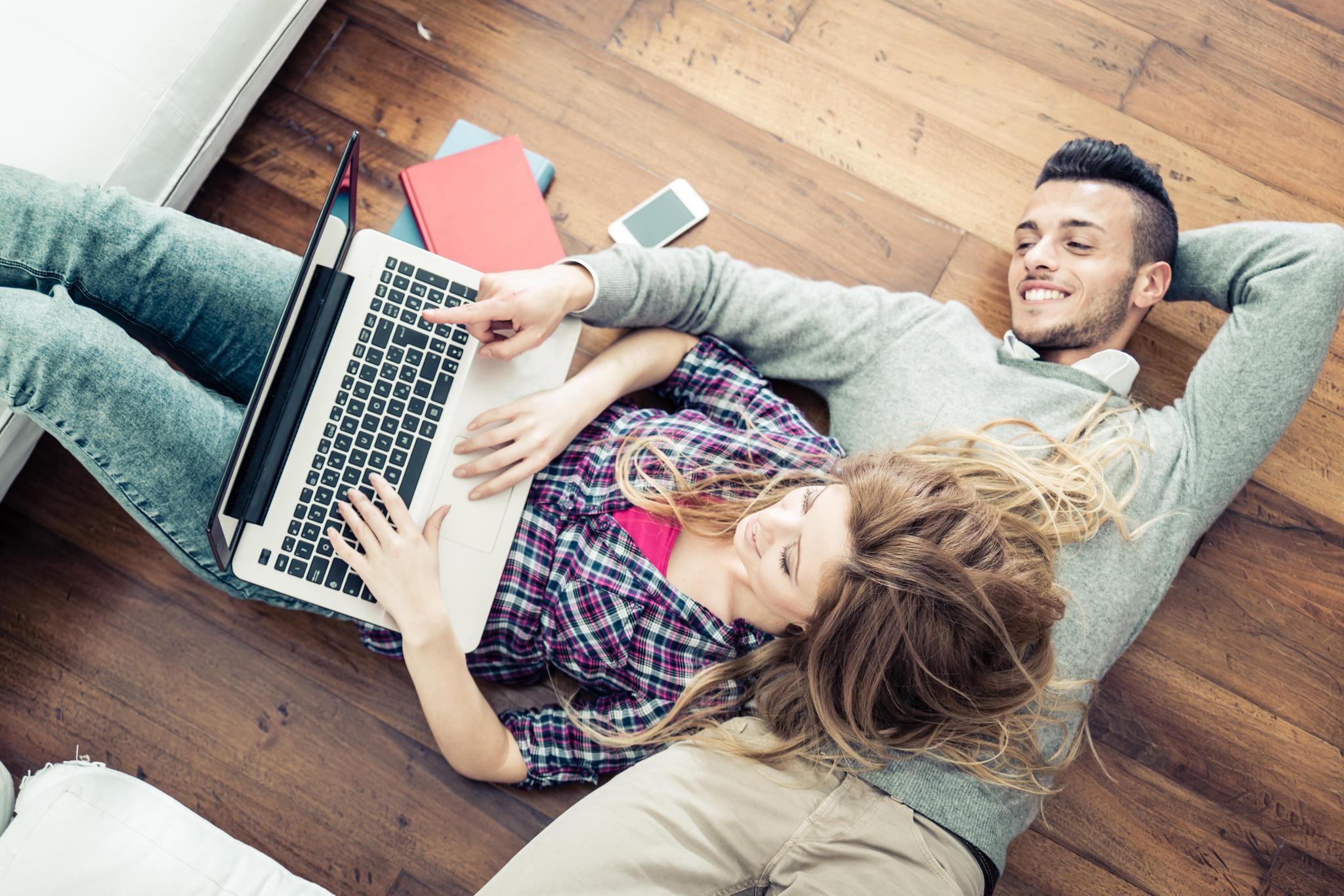 Junges Paar liegt auf dem Boden mit PC auf dem Bauch und lächelt