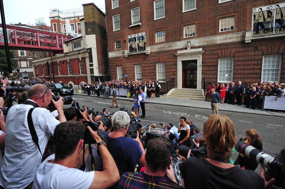 Kate, William und George sind umzingelt von Fotografen, Fans und Reportern.