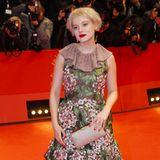 Jella Haase setzt bei der Berlinale auf den romantischen Stil. Zu dem auffälligen floralem Kleid kombiniert sie den Calypso Ohrclip und Théa Ring von Messika.