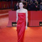Hannah Herzsprung entscheidet sich für eine eng anliegende rote Robe von Ralph Lauren. Das Kleid harmoniert schön mit ihrer Haarfarbe.