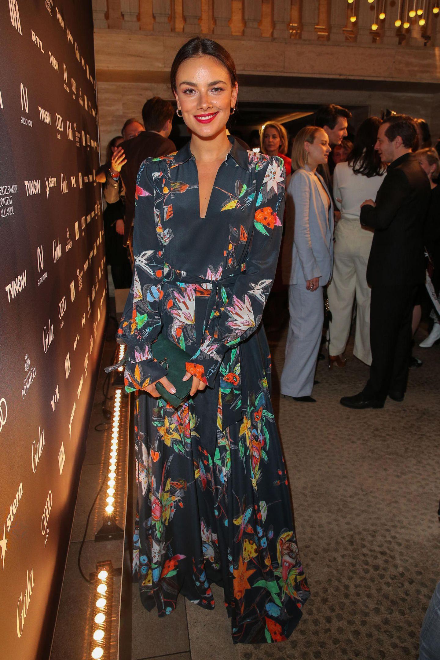 """Janina Uhse strahlt bei der """"Berlinale Opening Night"""" im leichten floralem Kleid. Die roten Lippen passen perfekt zum Outfit."""