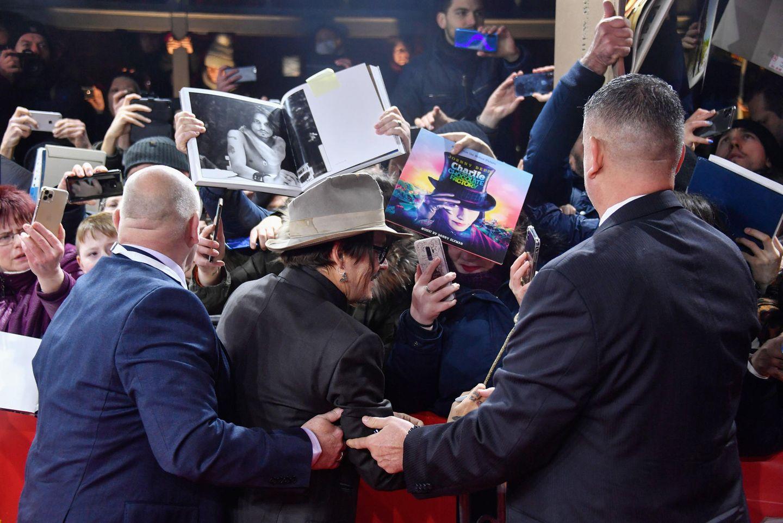 Johnny Depphat alle Hände voll zu tun, seinen treuen Fans gerecht zu werden. Fleißig gibt er Autogramme.