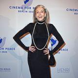 Best-Ager-ModelEveline Hall akzentuiert ihre gertenschlanke Figur mit einem bodenlangen, schwarzen Kleid und einer langen Perlenkette.